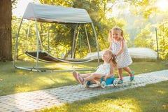 Petites filles blondes mignonnes montant une voiture de jouet en été Image stock