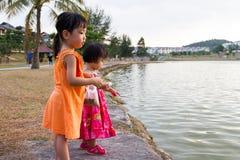 Petites filles chinoises asiatiques alimentant des poissons Photos stock