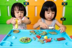 Petites filles chinoises asiatiques jouant avec de l'argile coloré Photo stock