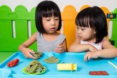 Petites filles chinoises asiatiques jouant avec de l'argile coloré Image libre de droits