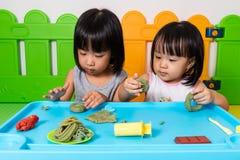 Petites filles chinoises asiatiques jouant avec de l'argile coloré Image stock