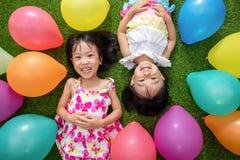 Petites filles chinoises asiatiques se trouvant sur l'herbe parmi le ballo coloré Photographie stock libre de droits