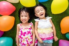 Petites filles chinoises asiatiques se trouvant sur l'herbe parmi le ballo coloré Photo libre de droits