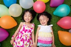 Petites filles chinoises asiatiques se trouvant sur l'herbe parmi le ballo coloré Images libres de droits