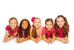 Petites filles d'isolement s'étendant sur le fond blanc image stock