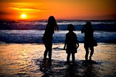 Petites filles dans un coucher du soleil Images stock