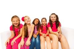 Petites filles de sourire s'asseyant sur le fond blanc Photos libres de droits