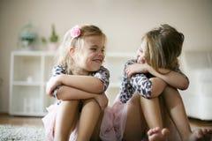 Petites filles de sourire s'asseyant sur le plancher Image libre de droits