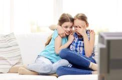 Petites filles effrayées observant l'horreur à la TV à la maison Image stock