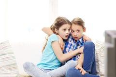 Petites filles effrayées observant l'horreur à la TV à la maison Photos libres de droits