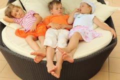 Petites filles et garçon se trouvant sur le grand fauteuil de cercle Photographie stock