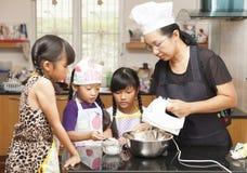 Petites filles et mère asiatiques faisant le gâteau mousseline Image stock