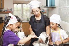 Petites filles et mère asiatiques faisant le gâteau mousseline Photos libres de droits