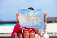Petites filles et maman adorables avec la carte de l'île Image stock