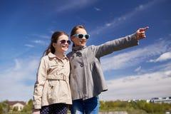 Petites filles heureuses étreignant et dirigeant le doigt Photos libres de droits