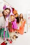 Petites filles heureuses dans le magasin se tenant parmi des robes Photographie stock