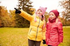 Petites filles heureuses dirigeant le doigt en parc d'automne Photographie stock libre de droits