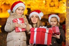 Petites filles heureuses et leur maman avec des présents Photographie stock libre de droits