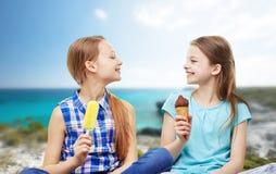 Petites filles heureuses mangeant de la glace au-dessus de la plage Image libre de droits