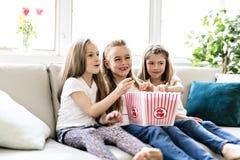 Petites filles heureuses observant le film de comédie à la TV et mangeant du maïs éclaté à la maison photo stock