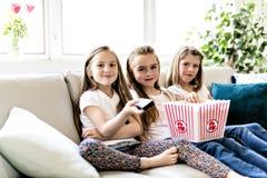Petites filles heureuses observant le film de comédie à la TV et mangeant du maïs éclaté à la maison image stock