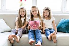 Petites filles heureuses observant le film de comédie à la TV et mangeant du maïs éclaté à la maison photographie stock libre de droits
