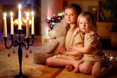Petites filles heureuses s'asseyant par une cheminée le réveillon de Noël Images stock
