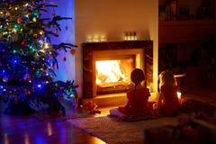 Petites filles heureuses s'asseyant par une cheminée le réveillon de Noël Photos stock