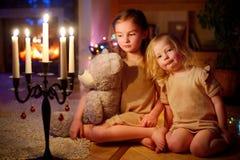 Petites filles heureuses s'asseyant par une cheminée le réveillon de Noël Photos libres de droits