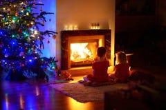 Petites filles heureuses s'asseyant par une cheminée le réveillon de Noël Photo libre de droits