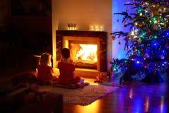 Petites filles heureuses s'asseyant par une cheminée le réveillon de Noël Image libre de droits