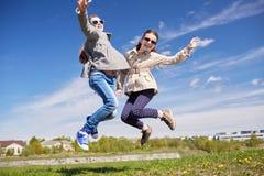 Petites filles heureuses sautant haut dehors Photographie stock libre de droits