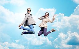Petites filles heureuses sautant haut par-dessus le ciel bleu Image libre de droits