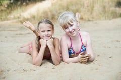 Petites filles heureuses sur la plage de sable photographie stock libre de droits