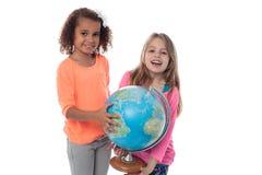 Petites filles jouant avec le globe Photographie stock