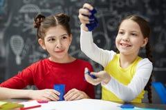 Petites filles jouant avec modeler l'argile en Art Class image libre de droits