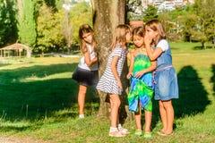 Petites filles jouant en parc et chuchotement photographie stock