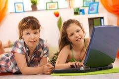 Petites filles jouant sur l'ordinateur à la maison Photographie stock