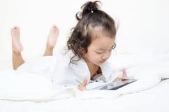 Petites filles jouant sur un dispositif de calcul de tablette photo libre de droits