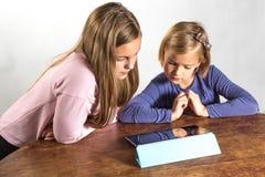 Petites filles jouant sur un dispositif de calcul de tablette images libres de droits