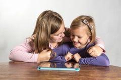 Petites filles jouant sur un dispositif de calcul de tablette photographie stock libre de droits