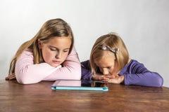 Petites filles jouant sur un dispositif de calcul de tablette images stock