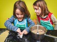 Petites filles jumelles faisant le tortellini à la maison fait o de boulettes de pâtisserie image stock