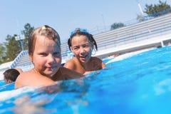 Petites filles mignonnes appréciant dans la piscine Image libre de droits