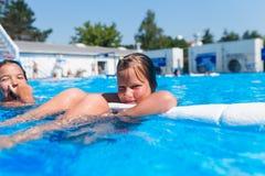 Petites filles mignonnes appréciant dans la piscine Photo stock