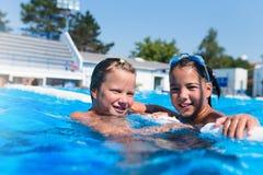 Petites filles mignonnes appréciant dans la piscine Photos libres de droits