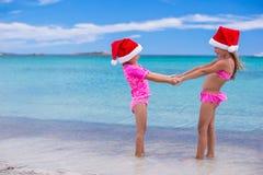 Petites filles mignonnes dans des chapeaux de Noël ayant l'amusement dessus Photo libre de droits