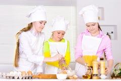 Petites filles mignonnes dans des chapeaux du ` s de chef et tabliers préparant la pâte dans t images libres de droits