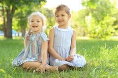 Petites filles mignonnes s'asseyant sur l'herbe verte Image libre de droits