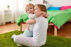 Petites filles ou soeurs heureuses étreignant à la maison Photo libre de droits
